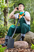 Gardener resting, talking on the phone — Stok fotoğraf