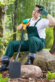 Exhausted gardener resting on a rock — Stock Photo