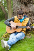 Man playing on guitar in forest — Stock fotografie