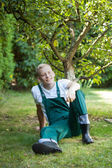Gardener resting in orchard — Stock Photo