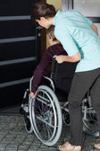 Nurse helping a disabled woman — Stock Photo