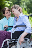 Nurse hugs an disabled woman — Stock Photo