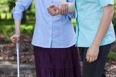 Elderly woman walking holding a nurse — Stock Photo