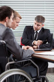 Disabled man talking with boss — Stock Photo