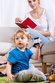 Child playing while mother is reading — Stock Photo