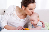 Mother kissing baby on sofa — Stock Photo
