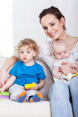 Mother with children on sofa — Stock Photo