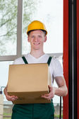 Workman holding a cardboard box — Stock Photo