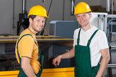 Workers standing next to machine — Stock Photo