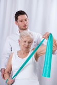 Physiotherapist exercising with patient — Stock Photo