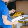 Delivery man looking at clipboard — Stock Photo #51161961