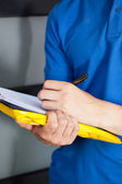 Close-up of a courier writing on clipboard — Stock Photo