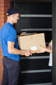 Delivery man giving parcel to homeowner — Stock Photo