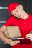Busy courier calling on mobile phone — Stok fotoğraf