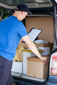 Courier and a car full of packages — Stok fotoğraf