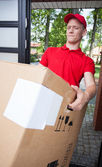 Delivery man holding a heavy box — Stock Photo