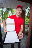 Courier showing a document on clipboard — Stock Photo