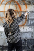 Young vandal drawing graffiti — Stock Photo