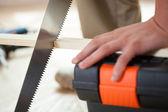 Man's hands using handsaw — Stock Photo