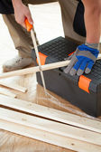 Man cutting boards with handsaw — Stockfoto