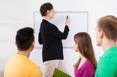 Teacher writing on whiteboard at classroom — Stock Photo