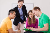 Teacher helping her students with homework — Stock Photo