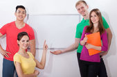 Students showing empty whiteboard — Stock Photo