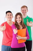 Happy students showing thumbs up sign — Стоковое фото