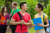 Multi-ethnic students with folders and backpacks — Stock Photo