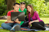 Friends sitting on blanket in park — Stock Photo