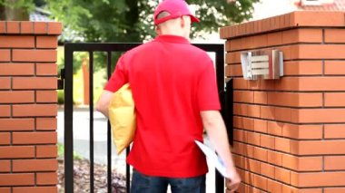Courier with package using building intercom — Stock Video