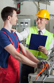 Controller talking with factory worker — Foto Stock