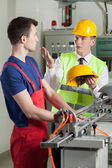 Inspector controlling safety during work at factory — Stock Photo