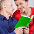Grandfather and granddaughter reading book — Stock Photo #51308699