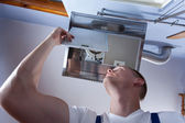 Fixing kitchen wall hood — Stock Photo