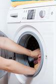 Hands putting laundry into washing machine — Stock Photo