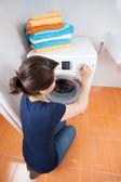 Woman adjusting dial on washing machine — Stock Photo