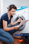 Woman trying to repair washing machine — Stock Photo