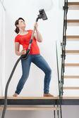 Girl during vacuuming floor — Stock Photo