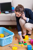 Businesswoman picking up toys — Stock Photo