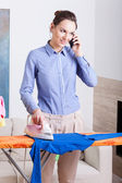 Mother talks on phone while ironing — Stock Photo