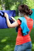 Woman removing laundry from clothesline — Stock Photo
