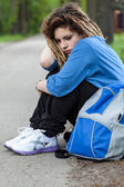 Sad girl with dreadlocks sitting on road — Stock Photo