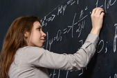 Portrait of a pretty student doing maths on a blackboard — Stock Photo