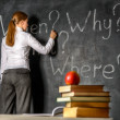 Student writing on blackboard — Stock Photo