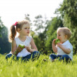 Little boy and girl eating apples on picnic in park — Stock Photo