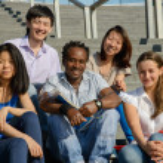 Multiethnic group of university students sitting on steps — Stock Photo