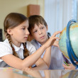 Stock Photo: Two shcoolchildren looking at globe