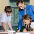 Stock Photo: Teacher helping little schoolchildren