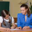 Stock Photo: Teacher helping schoolgirl
